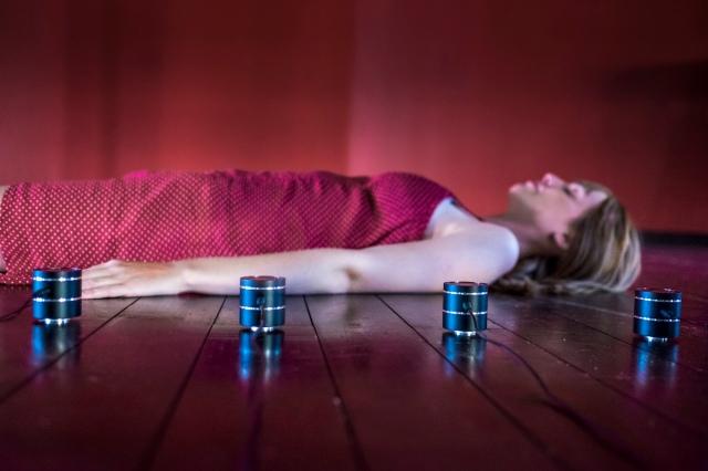 """Installazione """"Wooden Waves"""", Alessandro Perini. Originariamente realizzata per un mulino a vento in legno sulla costa occidentale della Svezia, questa installazione trasforma un pavimento di legno in un dispositivo vibrante per l'ascolto tattile. Stendendosi sulle doghe in legno, che vibrano grazie a otto diversi speaker a contatto, l'ascoltatore percepisce il suono e i suoi movimenti anche sotto forma di vibrazione che percorre tutto lo spazio del corpo. I suoni utilizzati nella composizione musicale sono esclusivamente derivati da registrazioni effettuate con microfoni a contatto posti su legno manipolato in vari modi."""